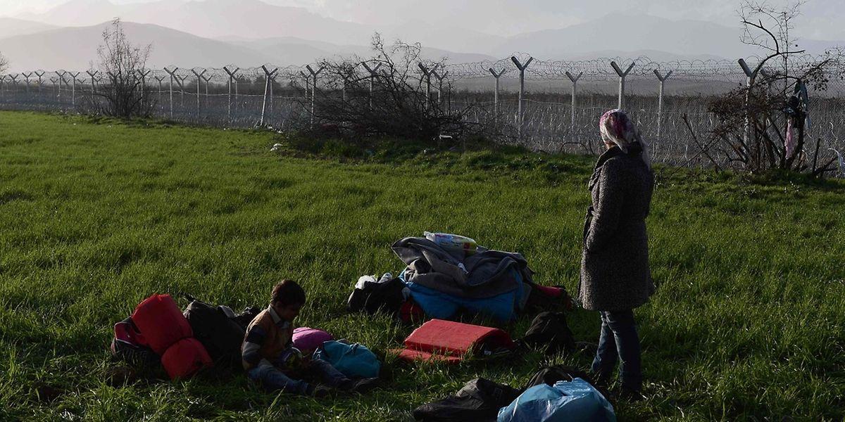 Eine Frau und ihr Kind blicken von Griechenland in Richtung Mazedonien. Ein Grenzzaun hindert sie an der Weiterreise.