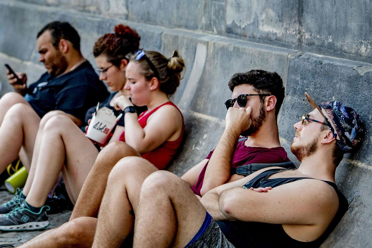 Tourists lean on a concrete wall as they seek cooling in the shade during A Amsterdam.