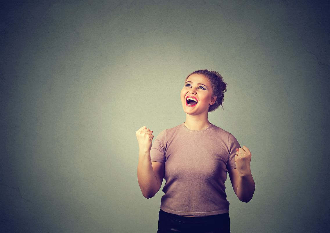 Closeup portrait happy successful student, woman winning, fists pumped celebrating success isolated on gray wall background. Positive human emotion facial expression. Life perception, achievement