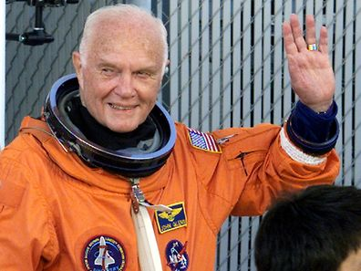 Astronaut John Glenn waves with crewmates as they depart crew quarters for the launching pad at the Kennedy Space Centre October 29, 1998.  REUTERS/File Photo
