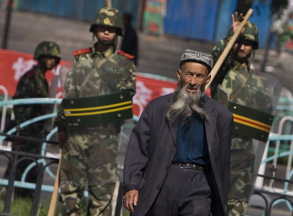 China, Ürümqi: Ein Angehöriger der uigurischen Minderheit in China geht in der Unruheregion Xinjiang in Nordwestchina vorbei an chinesischen Sicherheitskräften.