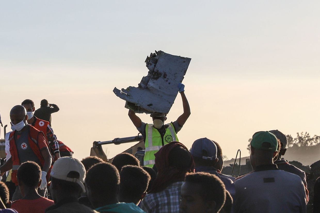 "A man carries a piece of debris on his head at the crash site of a Nairobi-bound Ethiopian Airlines flight near Bishoftu, a town some 60 kilometres southeast of Addis Ababa, Ethiopia, on March 10, 2019. - A Nairobi-bound Ethiopian Airlines Boeing crashed minutes after takeoff from Addis Ababa on March 10, killing all eight crew and 149 passengers on board, including tourists, business travellers, and ""at least a dozen"" UN staff. (Photo by Michael TEWELDE / AFP)"