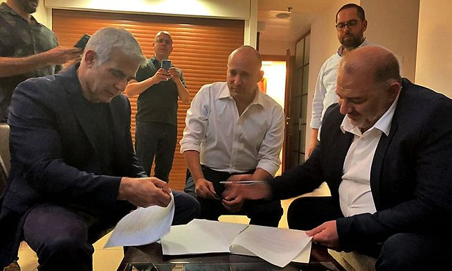 Head of the Arab Israeli Islamic conservative party Raam Mansour Abbas (R) signing  a coalition agreement with Israel's opposition leader Yair Lapid (L) and right-wing nationalist tech millionaire Naftali Bennett in Ramat Gan near the coastal city of Tel Aviv.