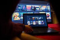 ILLUSTRATION - Ein junger Mann lässt sich eine Seite der Videostreaming-Firma Netflix am 14.09.2014 in Berlin von einem Laptop auf einem Fernsehbildschirm zeigen. Die in den USA populäre Online-Videothek Netflix geht im September auch in Deutschland auf Sendung. Netflix hat mit seinem Videostreaming-Abo den Fernsehmarkt in den USA aufgemischt und kommt dort mittlerweile auf 35,1 Millionen zahlende Kunden. Bestehende Konkurrenten in Deutschland sind Amazon, Maxdome oder Watchever. Foto: Bernd von Jutrczenka/dpa +++(c) dpa - Bildfunk+++ |