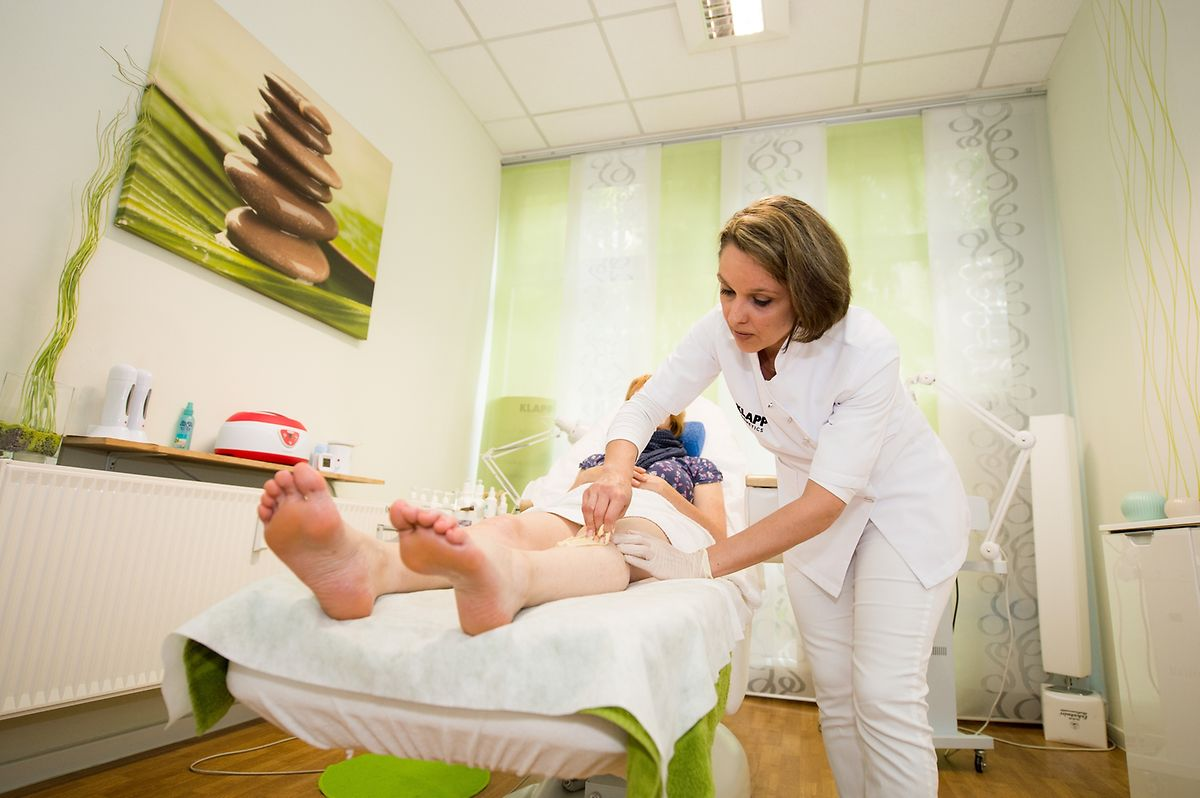 Kosmetikerin Inna Peter entfernt einer Kundin die Beinhaare beim Sugaring mit Hilfe einer Zuckerpaste.