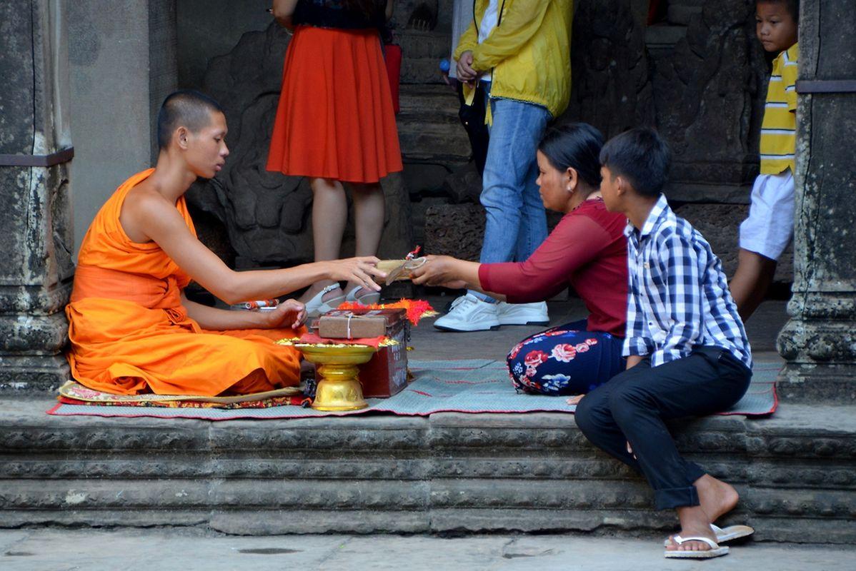 Le jeune bonze reçoit des offrandes de la part d'habitants de Siem Reap