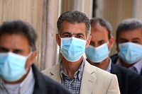 Libyans wearing protective face masks queue in front of a bank in the centre of the capital Tripoli on April 1, 2020, amidst the novel coronavirus pandemic crisis, on April 1, 2020. (Photo by Mahmud TURKIA / AFP)