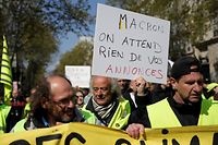 "A demonstrator holds a banner reading ""French President Macron, we don't expect anything from your announcements"" on April 13, 2019 in Paris, during a demonstration by the 'Yellow Vests' (gilets jaunes) movement on the 22nd consecutive Saturday. - The yellow vest protests against social inequality have proved the biggest challenge to French President since he came to power, taking much of the momentum out of his reformist agenda. (Photo by Thomas SAMSON / AFP)"