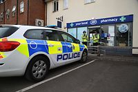 "Police officers are seen standing guard outside a local pharmacy in Amesbury, nine miles north of Salisbury, southern England, on July 4, 2018 where two people were found unconcious at a residence in Amesbury in circumstances that caused a major incident to be declared were believed to have visited.  Two people have been hospitalised in a critical condition for exposure to an ""unknown substance"" in the same British city where former Russian spy Sergei Skripal and his daughter were poisoned with a nerve agent earlier this year. British police declared a ""major incident"" after the couple, a man and a woman in their 40s, were discovered unconscious at a house in a quiet, newly-built area in Amesbury, with a number of locations cordoned off by police.  / AFP PHOTO / Geoff CADDICK"