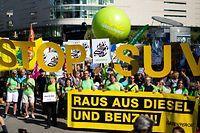 14.09.2019, Hessen, Frankfurt/Main: Demonstranten von Greenpeace stehen mit einem Transparent mit der Aufschrift «Raus aus Diesel und Benzin», dahinter fordern Demonstranten mit großen gelben Buchstaben «Stop SUV». Tausende Demonstranten wollen am ersten Publikumstag der Internationalen Automobilausstellung (IAA) für eine rasche Wende hin zu klimaschonender Mobilität eintreten. Foto: Marius Becker/dpa +++ dpa-Bildfunk +++