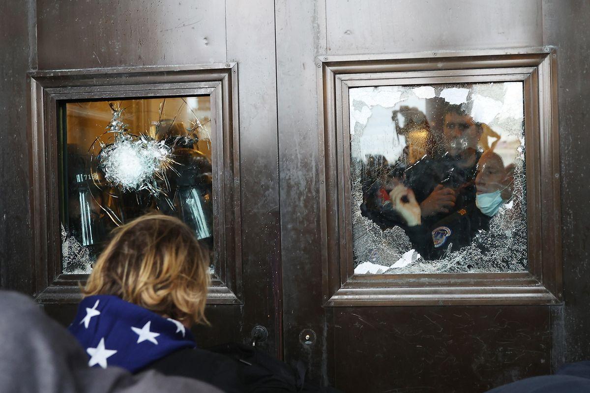 Ein Polizist blickt aus einer zerbrochenen Glasscheibe, während sich die Trump-Anhänger vor den Toren des Kapitols sammeln.