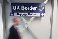 """11.06.2020, Großbritannien, Belfast: Ein Mann geht an einem Schild mit der Aufschrift: """"UKBorder - Baggage Reclaim"""" am internationalen Flughafen Belfast vorbei. Der Flughafen wird am Montag, 15. Juni, nach einer Corona-Zwangspause wiedereröffnet. Foto: Niall Carson/PA Wire/dpa +++ dpa-Bildfunk +++"""