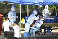 TOPSHOT - A health worker (2nd-L) wearing a protective suit takes a swab test on a woman in Beijing on June 16, 2020. - China reported another 27 domestically transmitted coronavirus cases in Beijing, where a fresh cluster linked to a wholesale food market has sparked WHO concern and prompted a huge trace-and-test programme. (Photo by Noel Celis / AFP)