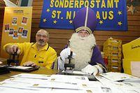 Heinz Grimm (l.) von der Deutschen Post und der Nikolaus aus der saarländischen Gemeinde St. Nikolaus, Rudolf Lange, stempeln auf diesem Archivbild aus dem Jahr 2008 mit dem Nikolaus-Sonderstempel der Post Briefe.
