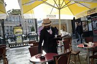 A memmer of staff clears a table at a cafe in Paris on May 19, 2021, as cafes, resteraunts and other businesses re-opened after closures during the coronavirus (Covid-19) pandemic. - Parisians have returned to their beloved cafe terraces and museums after a six-month Covid-forced hiatus, a glimmer of normal life resuming but India grappled with a record daily number of coronavirus deaths. (Photo by Lucas BARIOULET / AFP)