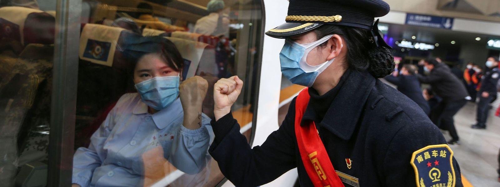 """""""Macht das Virus platt"""": Eine Zugbegleiterin verabschiedet medizinisches Fachpersonal, das von Nanchang ins Krisengebiet nach Wuhan reist."""