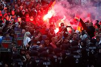 "TOPSHOT - Right wing demonstrators light flares on August 27, 2018 in Chemnitz, eastern Germany, following the death of a 35-year-old German national who died in hospital after a ""dispute between several people of different nationalities"", according to the police. - The far-right street movement PEGIDA called for a second day of protests in Chemnitz in ex-communist eastern Germany after the alleged fatal stabbing of a German man by a foreigner. (Photo by Odd ANDERSEN / AFP)"