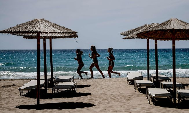 Women run on Falaserna beach on the western coast of Crete island on May 15, 2021. Tourists basked in the warmth, sun and crystal waters of Crete for long-awaited holidays as Greece kickstarted its tourism season after last year's pandemic misery.