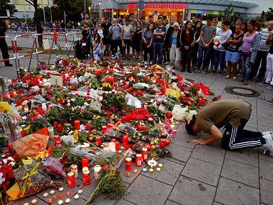 Vor dem Olympia Einkaufszentrum ist ein Meer aus Blumen zu sehen. Ein junger Mann betet für die Opfer.