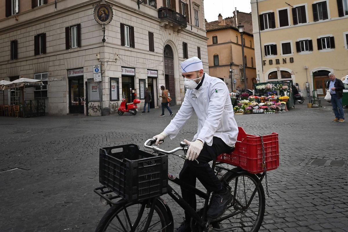 Ein Koch mit einer Atemschutzmaske radelt über den Campo Dei Fiori in Rom.