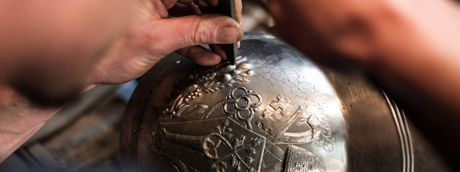 Mithilfe von Hammer und Meißel nimmt das Muster auf den Helmen Gestalt an.
