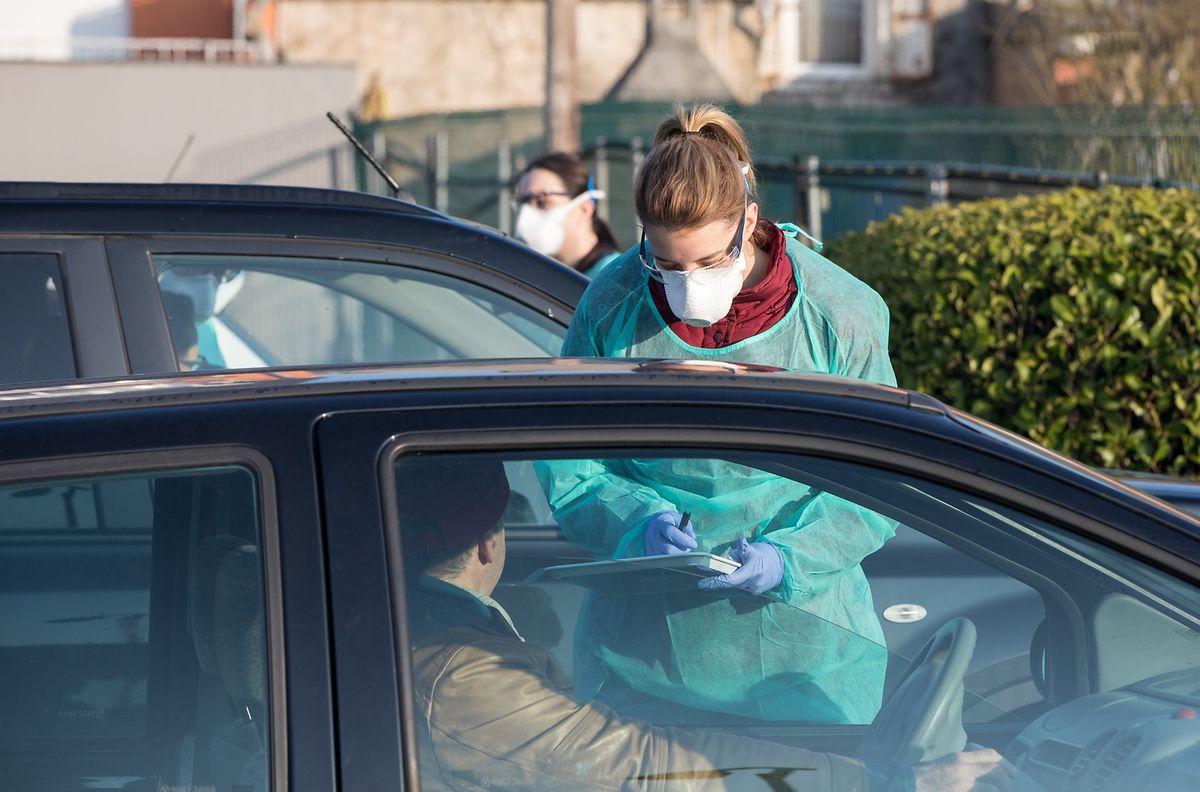 Die Mitarbeiter schützen sich mit Kitteln, Masken und Handschuhen bei den Tests vor einer möglichen Ansteckung - hier an der Drive-In-Station in Niederkerschen.