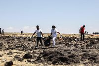 TOPSHOT - Rescue team carry collected bodies in bags at the crash site of Ethiopia Airlines near Bishoftu, a town some 60 kilometres southeast of Addis Ababa, Ethiopia, on March 10, 2019. - An Ethiopian Airlines Boeing 737 crashed on March 10 morning en route from Addis Ababa to Nairobi with 149 passengers and eight crew believed to be on board, Ethiopian Airlines said. (Photo by Michael TEWELDE / AFP)
