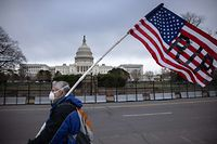 WASHINGTON, DC - JANUARY 08: A protester walks by as the American flag flies at half-staff at the U.S. Capitol on January 08, 2021 in Washington, DC. House Speaker Nancy Pelosi ordered the building's flags be flown at half-staff in honor of Capitol Police Officer Brian Sicknick, 42, who died after being injured during clashes with a pro-Trump mob at the Capitol on Jan. 6. Sicknick, a military veteran, was a 12-year member of the force.   John Moore/Getty Images/AFP == FOR NEWSPAPERS, INTERNET, TELCOS & TELEVISION USE ONLY ==