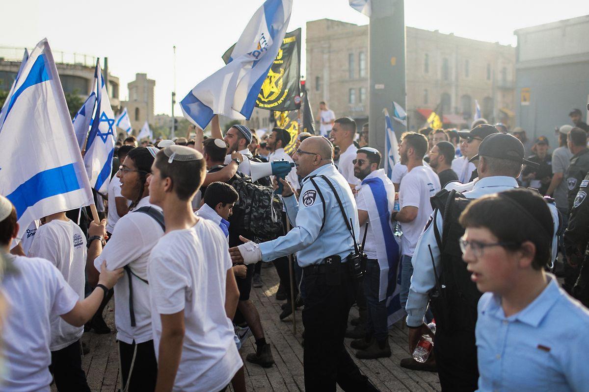 Israelis gehen am Jerusalemtag mit Nationalfahnen in Richtung der Schutzräume, nachdem Sirenensignale ertönten.