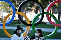 "Mask-clad people pose with an installation of the Olympic rings in Tokyo on February 28, 2020. - The International Olympic Committee is ""committed"" to holding the 2020 Games in Tokyo as planned despite the widening new coronavirus outbreak, the body's president has pledged. (Photo by CHARLY TRIBALLEAU / AFP)"
