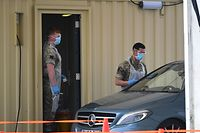 """Members of Britain's Army wearing PPE (personal protective equipment), including gloves, an apron, a face mask and eye protection as a precautionary measure against COVID-19, prepare to test a workjer of Britain's NHS (National Health Service) at a coronavirus COVID-19 testing centre set up in a car park at Ebbsfleet International Railway Station, in Ebbsfleet, south east of London, on April 27, 2020. - Prime Minister Boris Johnson on Monday made his first public appearance since being hospitalised with coronavirus three weeks ago, saying Britain was beginning to """"turn the tide"""" on the outbreak but rejecting calls to ease a nationwide lockdown. (Photo by Ben STANSALL / AFP)"""