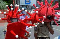 Polícias indianos com capacetes ilustrativos do SARS-CoV-2 para sensibilizar a população para a adoção das medidas sanitárias.