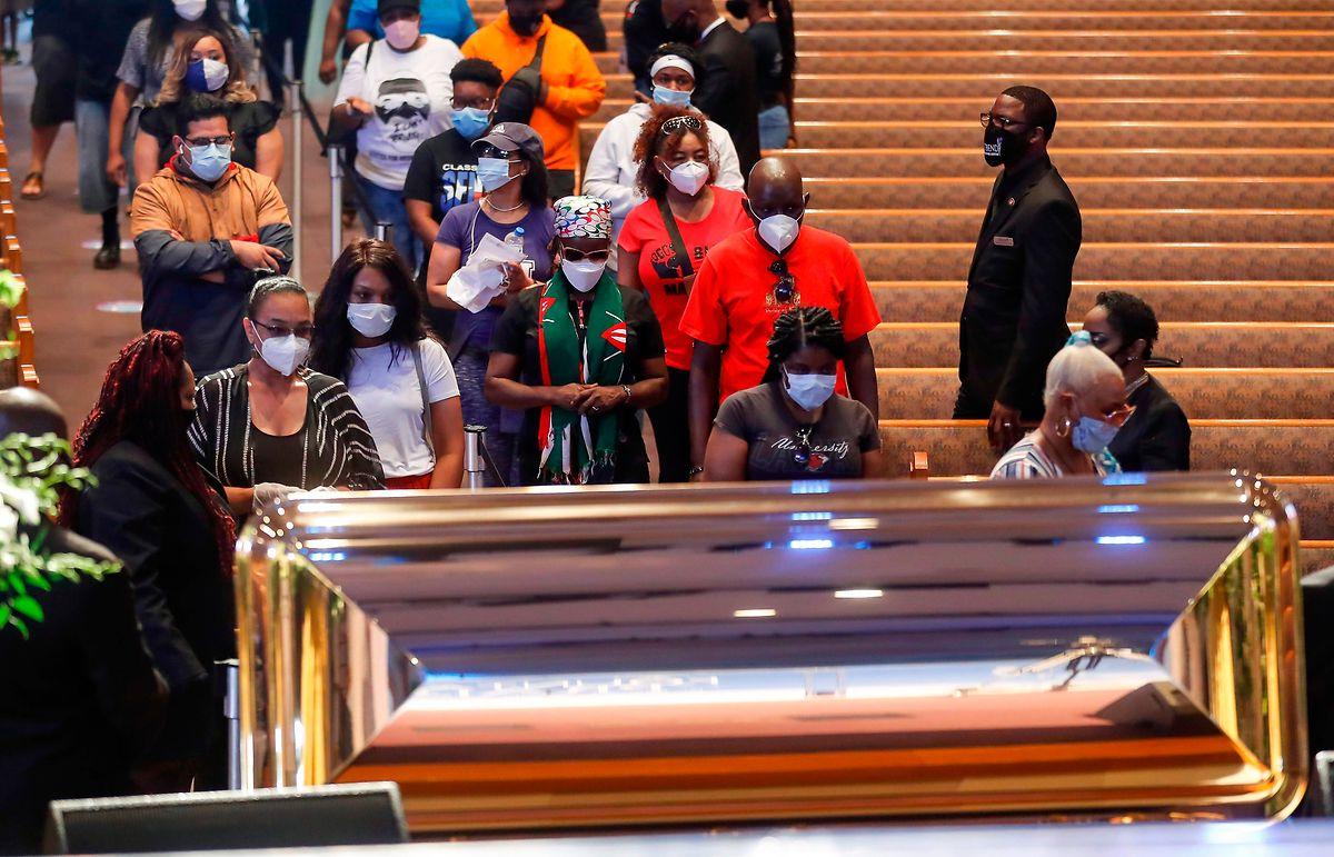 Trauergäste vor dem Sarg.