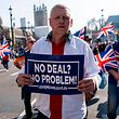 """Pro-Brexit demonstrators hold placards as protesters gather in Parliament Square in central London on March 29, 2019. - British MPs on Friday rejected Prime Minister Theresa May's EU divorce deal for a third time, opening the way for a long delay to Brexit -- or a potentially catastophic """"no deal"""" withdrawal in two weeks. (Photo by Niklas HALLE'N / AFP)"""