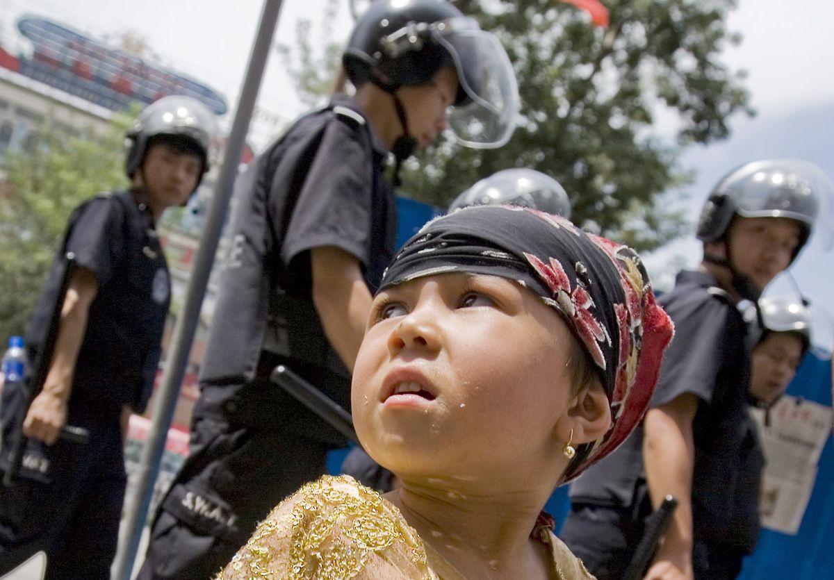 Ein junges Mädchen, das der ethnischen uigurischen Minderheit angehört, neben chinesischen Sicherheitskräften.