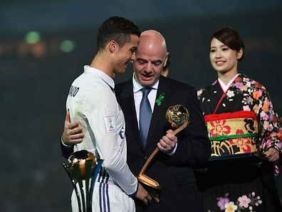 FIFA president Gianni Infantino (C) gives the Golden Ball trophy to Real Madrid's forward Cristiano Ronaldo (L)