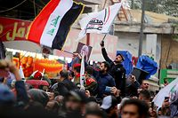 """Mourners wave the national flag and the Hashed al-Shaabi flag as they carry the portrait Iraqi paramilitary chief Abu Mahdi al-Muhandis during a funeral procession, for Muhandis and Iranian military commander Qasem Soleimani, in Kadhimiya, a Shiite pilgrimage district of Baghdad, on January 4, 2020. - Thousands of Iraqis chanting """"Death to America"""" joined the funeral procession Saturday for Iranian commander Qassem Soleimani and Iraqi paramilitary chief Abu Mahdi al-Muhandis, both killed in a US air strike. (Photo by SABAH ARAR / AFP)"""