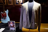 "Kurt Cobain's cardigan from Nirvana's 1993 MTV Unplugged performance is on display at the Hard Rock Cafe in New York City ahead of the auction of Julien's Auctions on October 21, 2019 in New York City. - A quarter century after grunge's enigmatic rhapsodist took his own life, Kurt Cobain's iconic cigarette-singed cardigan worn during Nirvana's 1993 ""Unplugged"" performance is up for sale. The tattered faded green button-up sweater with dark stains and a burn hole could go for at least $200,000 to $300,000, according to pre-bidding estimates from Julien's Auctions, which says rock and roll memorabilia has become a major investor's market. (Photo by Johannes EISELE / AFP)"