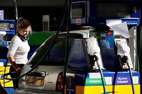 A motorist refills the fuel tanks of their vehicle, opposite tapped-off petrol and diesel pumps, at a petrol station in Leyton, east London on September 29, 2021. - British troops are expected to be deployed within days to help ease a fuel supply crisis, the government said on Wednesday, as the retail and hospitality sectors called for foreign workers to be allowed to fill post-Brexit vacancies. (Photo by Tolga Akmen / AFP)