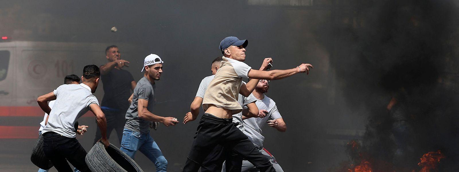 Palästinensische Demonstranten werfen am Freitag mit Steinen auf die Sicherheitskräfte.