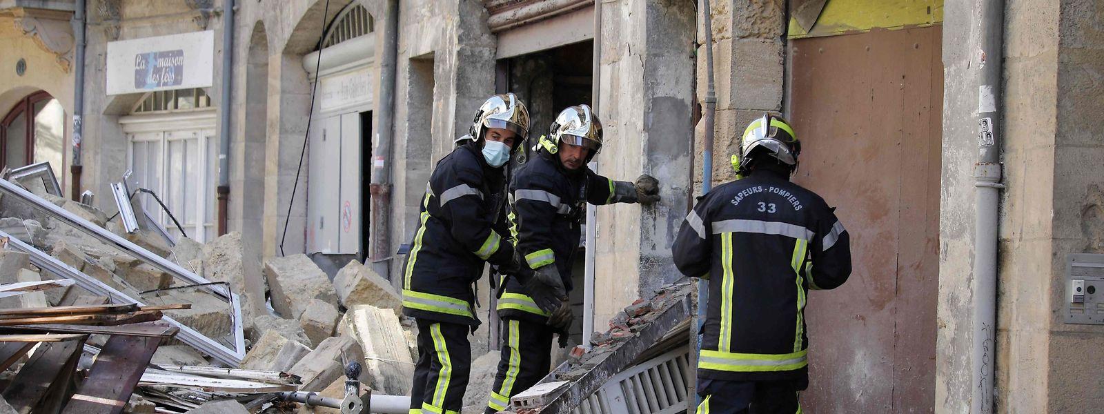 Feuerwehrleute vor den Trümmern der eingestürzten Häuser.