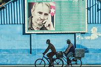 """(FILES) In this file photo men ride on their bicycles near a poster of Cuban late leader Fidel Castro in Havana, on July 12, 2021. - The United States on July 13, 2021 urged Cuba to end internet restrictions imposed after unprecedented protests and renewed a call for the release of detained demonstrators. """"We call on Cuba's leaders to demonstratate restraint (and) respect for the voice of the people by opening all means of communciation, both online and offline,"""" State Department spokesman Ned Price told reporters. (Photo by YAMIL LAGE / AFP)"""