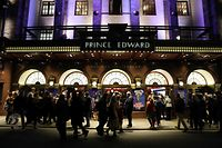 """Theatre-goers wearing masks arrive for an evening show of """"Mary Poppins"""" at the Prince Edward Theatre on March 12, 2020 in the theatres and restaurants district of West End in London. - Britain on March 12 said up to 10,000 people in the UK could be infected with the novel coronavirus, as it announced new measures to slow the spread of the outbreak. Johnson told a news conference the government was """"considering the question of banning major public events such as sporting fixtures"""" as part of its contingency plans. But scientists currently advised there was more risk of transmission in smaller venues than among large crowds. (Photo by Isabel INFANTES / AFP)"""