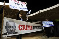 Supporters of retired Israeli General Benny Gantz, one of the leaders of the Blue and White (Kahol Lavan) political alliance, protest against his rival Prime Minister Benjamin Netanyahu (picture) as the former gives a press conference (unseen) in Tel Aviv on January 25, 2020. - US President Donald Trump said on January 23 he will release a long-delayed plan for Mideast peace before a meeting in Washington next week with Israeli Prime Minister Benjamin Netanyahu and his rival Benny Gantz. (Photo by EMMANUEL DUNAND / AFP)