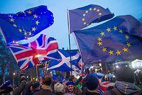 """ARCHIV - 13.03.2019, Großbritannien, London: Pro-Brexit Demonstranten der UK Independence Party (UKIP) und Demonstranten gegen den Brexit demonstrieren vor dem Parlament in Westminster. EU-Flaggen, eine Nationalflagge von Großbritannien (l, unten) und eine Flagge Schottlands (M, unten) sind dabei zu sehen. in Großbritannien haben kurz vor dem ursprünglich geplanten Ausstieg des Landes aus der Europäischen Union mehr EU-Bürger gearbeitet als ein Jahr zuvor. (Zu dpa """"In Großbritannien arbeiten mehr EU-Bürger als vor einem Jahr"""") Foto: Om1/RMV via ZUMA Press/dpa +++ dpa-Bildfunk +++"""