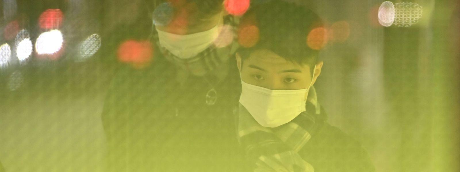 Passanten mit Atemschutzmasken in China: Die Ansteckungsgefahr in Zusammenhang mit der neuen Lungenkrankheit wird für Menschen in China immer größer.