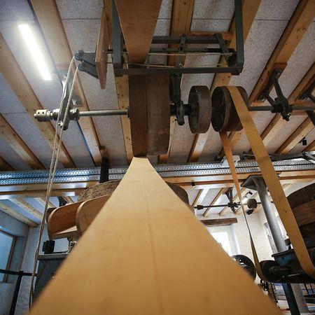 Der Mahlraum wird fast ganz von der noch erhaltenen und restaurierten Mühlentechnik, den Mahlsteinen und den Treibriemen ausgefüllt.