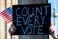 """04.11.2020, Berlin: Eine Teilnehmerin auf der Kundgebung unter dem Motto «Friedlicher Übergang der Präsidentschaft und eine demokratische USA» hält ein Schild mit der Aufschrift """"Count Every Vote"""" und eine Mini-US-Flagge hoch. Mehr als 200 Millionen Amerikaner waren aufgerufen, einen neuen Präsidenten und die Abgeordneten des Repräsentantenhauses zu wählen. Foto: Fabian Sommer/dpa +++ dpa-Bildfunk +++"""
