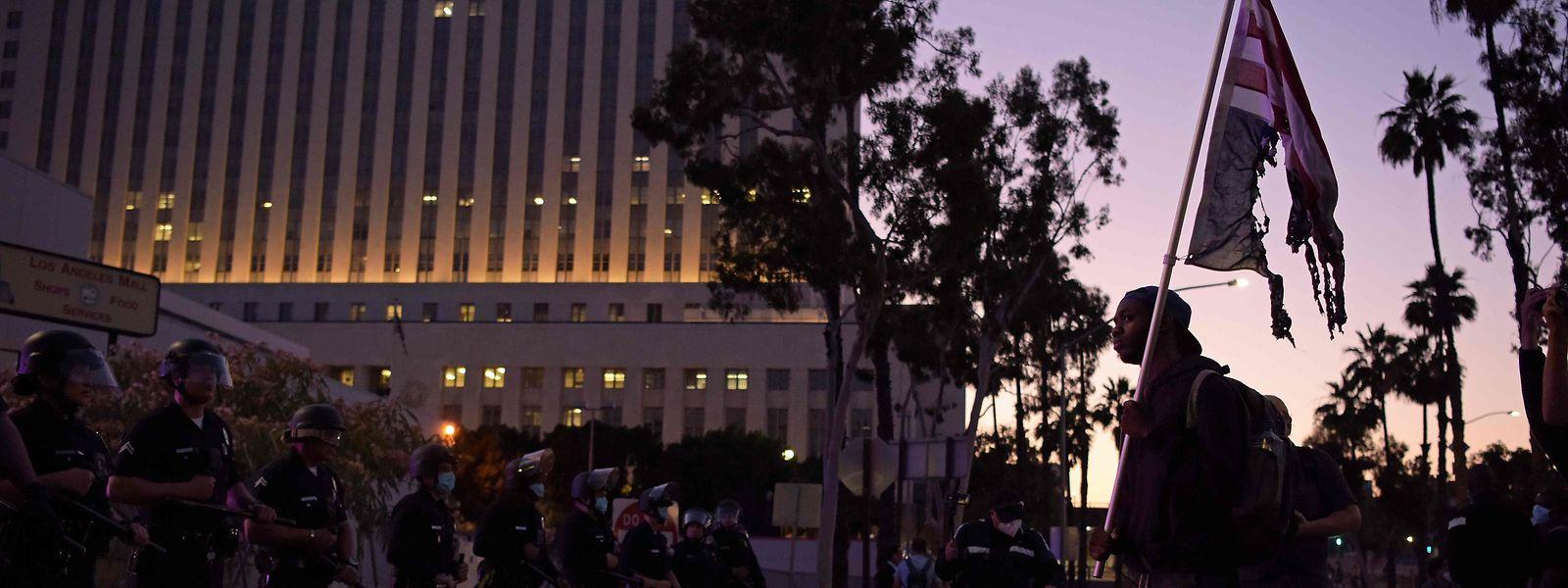 Die Lage ist explosiv und kann jederzeit wieder eskalieren. Ein Mann demonstriert mit einer zerrissenen US-Flagge gegen die Polizeigewalt.