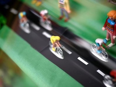 Figurines representing cyclists of the Tour de France are displayed in a shop window in Saint-Lo, Normandy, on June 29, 2016, three days before the start of the 103rd edition of the Tour de France cycling race. The 2016 Tour de France will start on July 2 in the streets of Le Mont-Saint-Michel and ends on July 24, 2016 down the Champs-Elysees in Paris. / AFP PHOTO / LIONEL BONAVENTURE